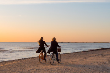 Women ride a bike along the seashore. Very beautiful sunset landscape. Great holiday by the sea. Evening bike ride.