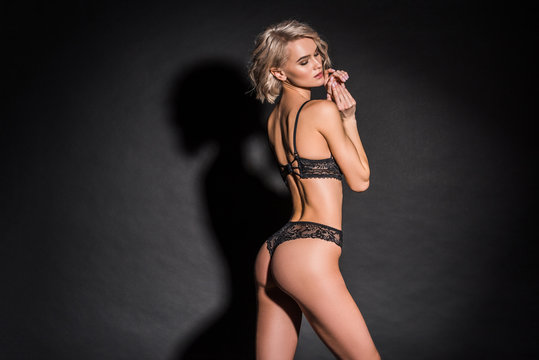 beautiful seductive girl in lace lingerie posing on black with copy space
