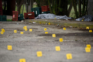 Covered bodies of dead people are seen near bullet casings on the ground at a crime scene after a shootout in the municipality Tuzamapan