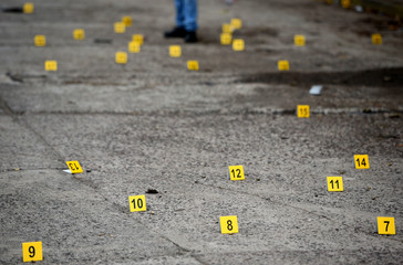 People stand near bullet casings on the ground at a crime scene after a shootout in the municipality Tuzamapan