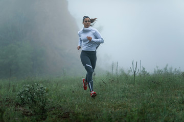Active young woman jogging through misty park. Wall mural