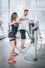 EMS electro stimulation women exercises with coach in modern gym