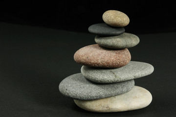 Seven pebbles pyramid over dark