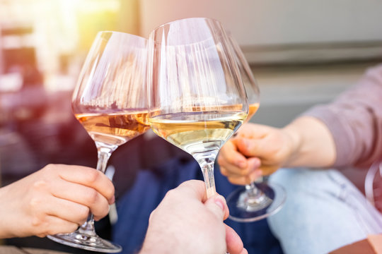 Clinking glasses with white wine and toasting. Three glasses of wine close up. Copy space