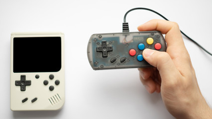 hand holding retro games isolated on a white background. focus on console and hands.