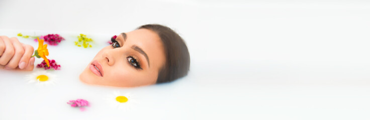 Foto op Plexiglas Spa attractive Caucasian model in milk bath with perfect teeth, face, skin and lips, and natural make up, beauty and spa concept with flowers and tropical leaves
