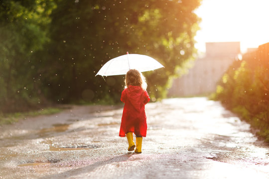 Happy child  with an umbrella playing out in the rain in the summer outdoors