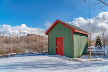 Exterior of a wooden storage shed built on a snow covered ground in winter