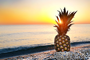 Single ripe organic pineapple on the sandy tropical beach over beautiful setting sun seascape background. Vintage toned image of exotic fruit in soft sunset light. Close up, copy space. Wall mural