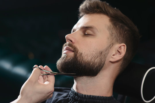 Getting perfect shape. Close-up side view of young bearded man getting beard haircut by hairdresser or barber at barbershop