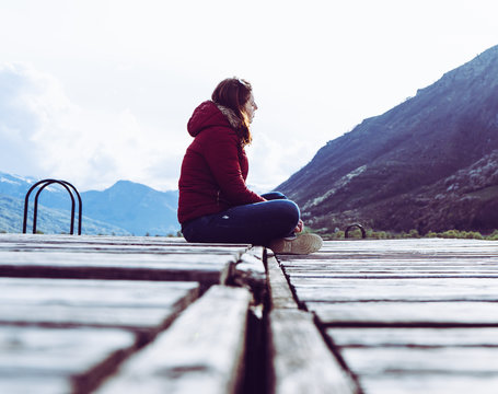 A young girl sits on the edge of a wooden pier and looks into the distance surrounded by mountains in Plav lake