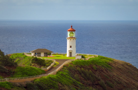Kilauea Point Lighthouse glowing in the summer sun against a blue sky and ocean, Kauai, Hawaii, USA
