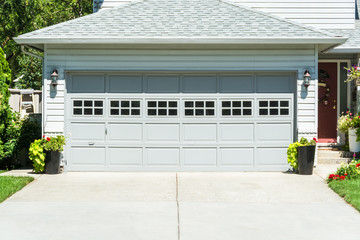 Wide garage door of residential house and concrete driveway in front