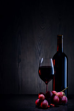 Red wine in glass and bottle and bunch of grapes on wooden table