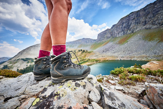 a young woman wearing hiking boots and trekking around an alpine mountain lake