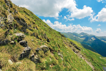 slope of the mountain ridge. summer landscape with rocks among grass and clouds on the blue sky. popular destination of Romania Carpathians