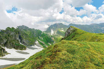 fagaras mountain ridge in summer. spots of snow on grass of steep slope. rocky tops. cloudy weather. romania landscape