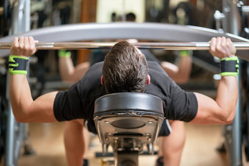 sport, bodybuilding, lifestyle and people concept - young man with barbell flexing muscles and making bench press in gym .