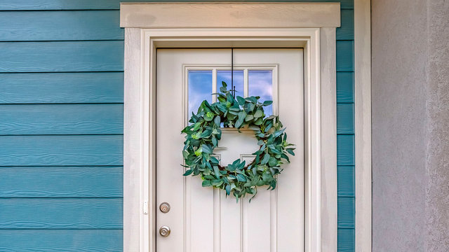 Panorama Facade of a home with a simple leafy wreath hanging on the white front door