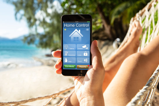 Woman Using Smart Home On Mobile Phone At Beach
