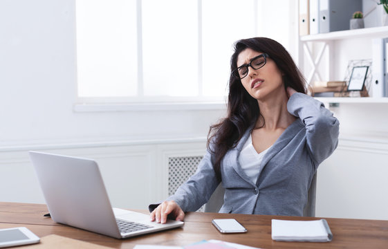 Tired Businesswoman Suffering From Neck Pain In Office