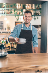 Fototapeta Friendly barista giving cup of coffee and smiling obraz