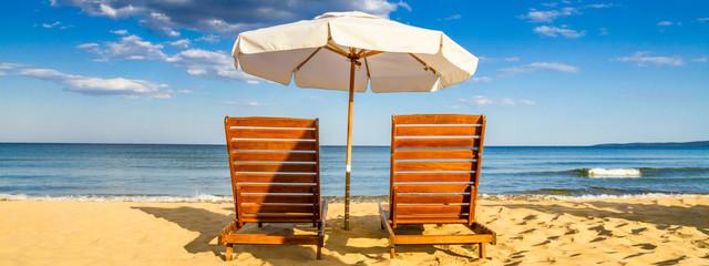 Papiers peints Plage Coastal landscape - Beach umbrellas and loungers on the sandy seashore near city of Sozopol in Bulgaria