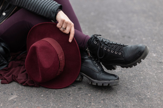 Young woman with an elegant vintage purple hat in pants in leather fashionable black shoes is sitting on the asphalt. Stylish women's headdress and shoes. Modern street style. Close-up.