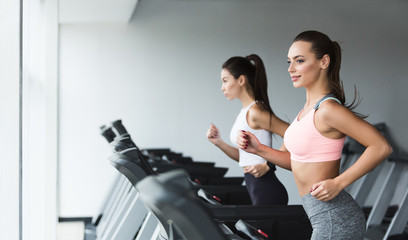 Sporty women running on treadmill, doing cardio workout in gym Fototapete