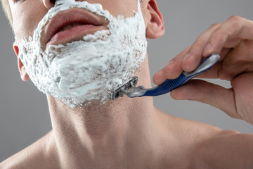 Young man shaving his stubble with disposable razor