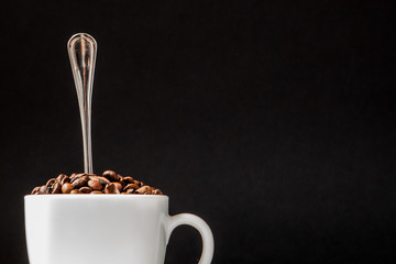 Black coffee in white cup and coffee beans on black background. Top view, space for text
