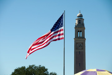 Flag of the United States at the Parade Ground in Louisiana State University, with the War Memorial Tower in the background, Baton Rouge, Louisiana, USA.