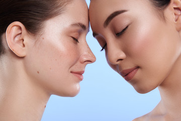 Close up of two interracial attractive women situating against blue background Fototapete