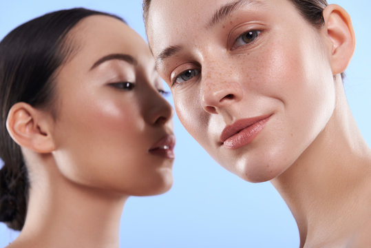 Close up portrait of attractive interracial women situating against blue background