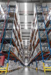 galpão logistica e distribuição caixas trabalhadores e empilhadeira em operação