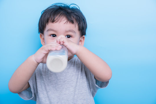 Asian little baby boy drinking milk from bottle glass on blue background