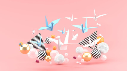 A paper bird among colorful balls on a pink background.-3d rendering.