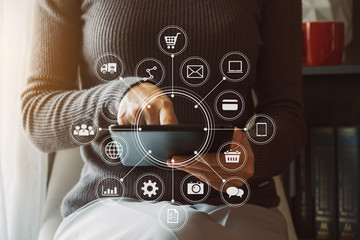 Woman using smart phone for mobile payments online shopping,omni channel,sitting on table,virtual icons graphics interface screen in morning light