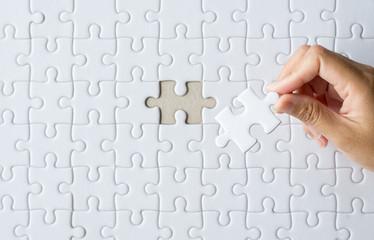 Hands women putting jigsaw puzzle white color,Puzzle pieces grid,Concept partnership business successful teamwork,Top viex,Copy space for text