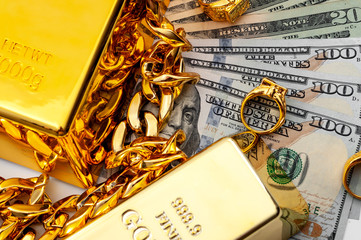 Jewelry buyer, pawn shop and buy and sell precious metals concept theme with a pile of cash in US dollars, golden rings, necklace bracelet and gold bullion isolated on white background