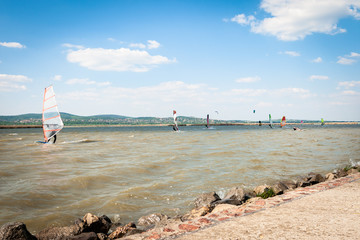 Windsurfer surfing the wind on waves on a lake on a summer day. Recreational water sport.