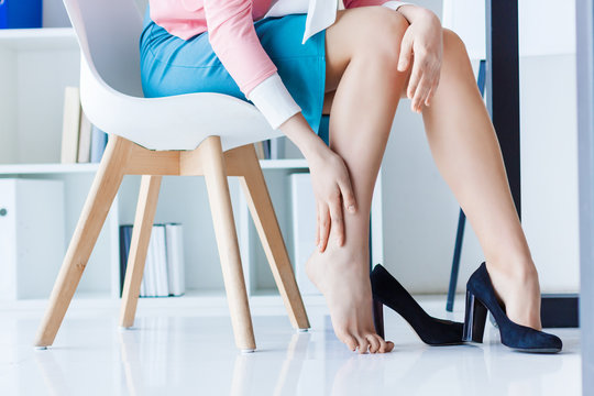 Business woman in strict colorful clothes sitting in chair, hold legs has pain varicose veins symptom, arthritis, arthrosis, joint disease from black high heels. Office worker health problem concept.