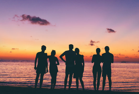 Friendship and vacation. Silhouette of people enjoying sunset on the sea shore.
