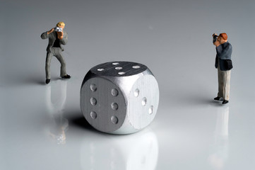 Two Miniature Photographertakes picture of a silver steel dice on white background
