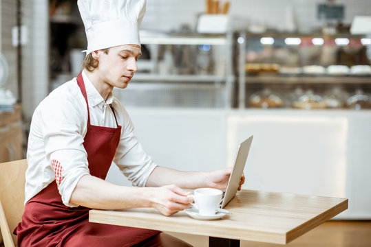 Chef cook in apron and hat working with laptop and drinking coffee in the pastry shop or cafe