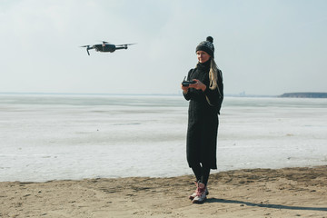 Woman using drone near frozen sea