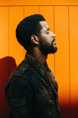 African mixed race man with beard. Portrait on orange background