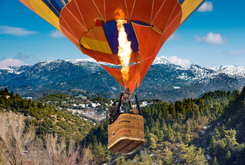 Poster Ballon passengers into hot air balloon basket and flames flying from Mainalo to Helmos mountains.Arcadia, Greece