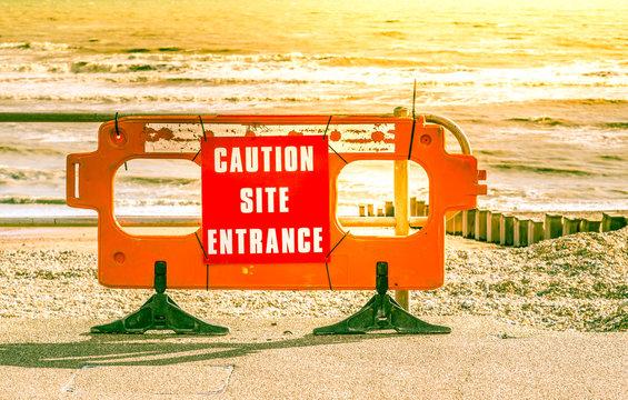 Caution Site Entrance sign on beach, South Coast, UK