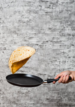Frying pan with flying pancake in hand on gray wall background